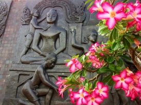 THAILAND: Gorgeous stone Buddha in Sukothai Historical Park, framed by pretty pink flowers.